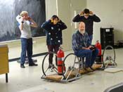 Students protect their ears before demonstrating the rocket car. Professor Paul Schwoebel is the rocket car passenger