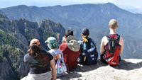 REU 2018 program participants sitting on the edge at the top of Sandia Mountain